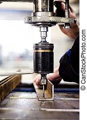 Ingeniero industrial usando una máquina mecánica en un factor
