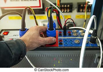 Ingeniero técnico electricista con dispositivo de prueba para las protecciones de relé de energía de líneas de alto voltaje, transformadores y generadores. Herramientas de mantenimiento. El hombre de servicio conecta los enchufes con el dispositivo de prueba.