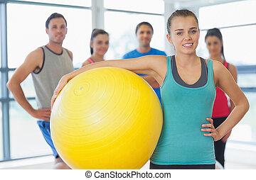 Instructor haciendo ejercicio con clase de aptitud en el fondo