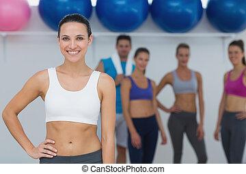 Instructora femenina con clase de gimnasia en el fondo