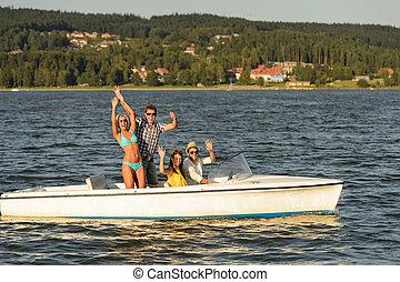 Jóvenes amigos disfrutando el verano en lancha rápida