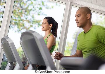 Jóvenes ejercitándose y corriendo en el gimnasio