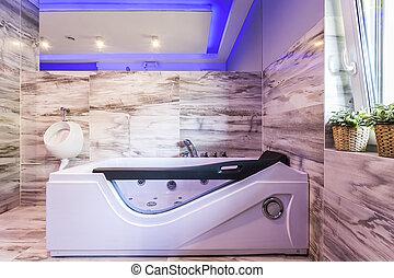 Jacuzzi confortable y orinal en el baño de baldosas
