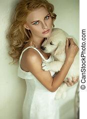 Joven belleza rubia abrazando a un perrito blanco