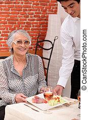 Joven camarero sirviendo a una mujer mayor en un restaurante
