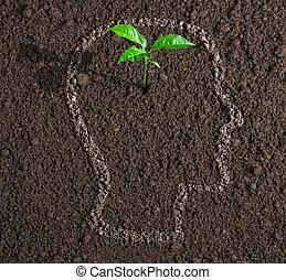 Joven crecimiento de la idea dentro del contorno de la cabeza humana en el concepto del suelo