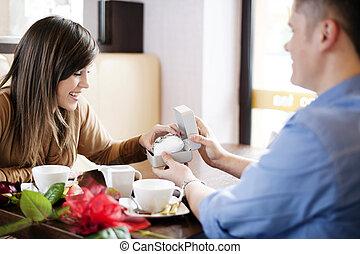Joven dando un reloj a su novia el día de San Valentín