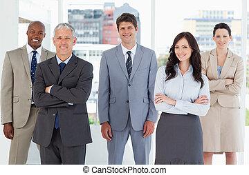 Joven ejecutivo sonriente parado en medio de la habitación entre sus colegas