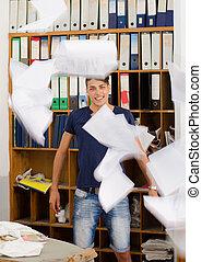 Joven en una oficina muy desordenada con documentos volando