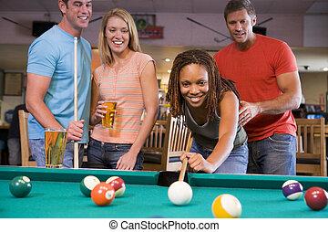 Joven enseñando a una joven a jugar al billar