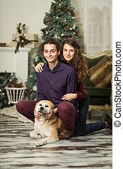 joven, feliz, piso, abrazar, pareja, navidad, perro, árbol, sentado