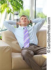 Joven hombre de negocios relajado con las manos detrás de la cabeza en el trabajo