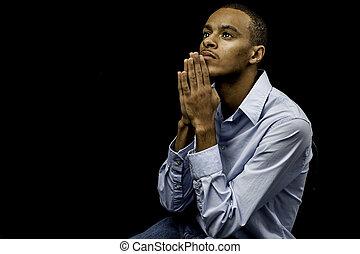 Joven hombre negro rezando