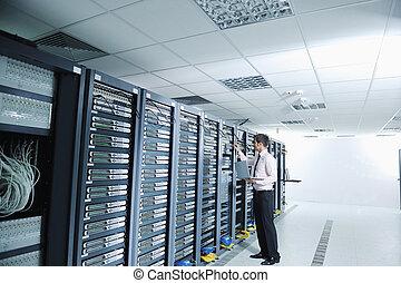 Joven ingeniero en la sala de servidores del centro de datos