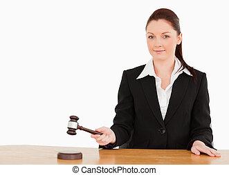 Joven juez golpeando un martillo sonriendo a la cámara