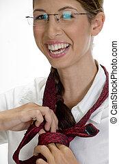 Joven mujer feliz atando su corbata