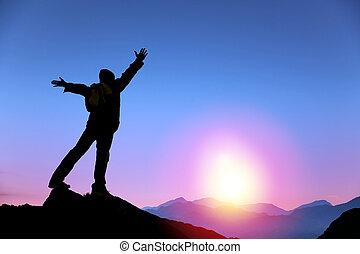 Joven parado en la cima de la montaña y mirando el amanecer