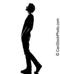 Joven silueta caminando mirando hacia arriba