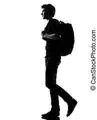 Joven silueta mochilero caminando