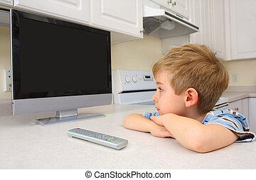 Joven viendo la tele en la cocina