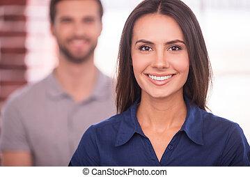 Joven y exitoso. Hermosa joven mirando a la cámara y sonriendo mientras el hombre está detrás de ella