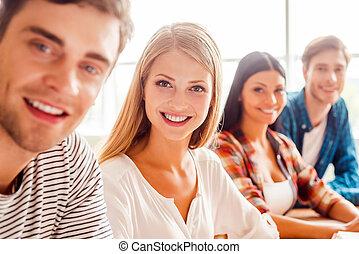 Joven y hermosa. Grupo de jóvenes felices mirando a la cámara y sonriendo mientras se sientan en una fila en el aula