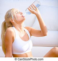 Jovencita bebiendo agua embotellada