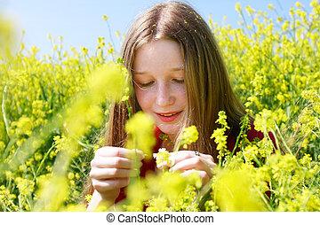 Jovencita con cabello largo en flores amarillas