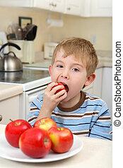 Jovencito comiendo una manzana