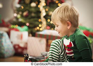 Jovencito disfrutando la mañana de Navidad cerca del árbol