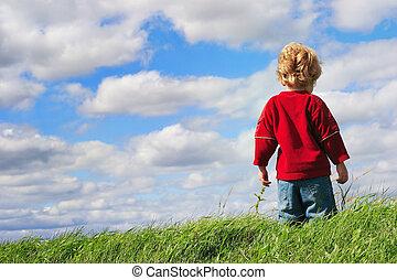 Jovencito parado en la cima de una colina