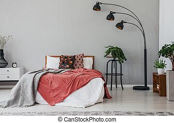 Lámpara de estilo negro en el elegante interior del dormitorio con cómoda cama doble, plantas, y mesa de noche, foto real con espacio de copia en la pared