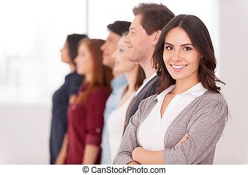 Líder confiado. Joven atractiva sosteniendo brazos cruzados y sonriendo mientras un grupo de gente detrás de ella en fila