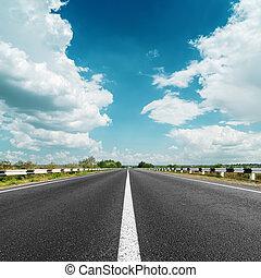 Línea blanca en camino de asfalto y nubes sobre él
