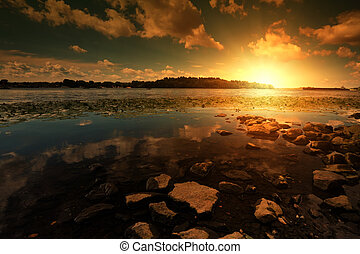Línea costera con piedras y puesta de sol