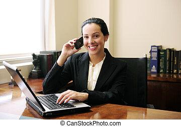 La abogada de la oficina hablando por teléfono y usando la laptop