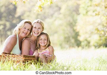 La abuela con la hija adulta y el nieto de picnic