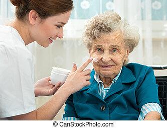 La anciana es asistida por la enfermera en casa
