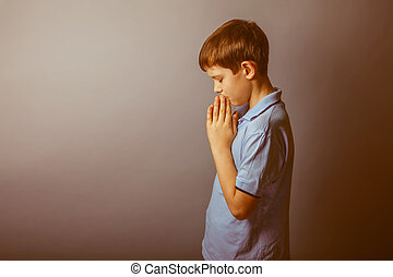 La aparición en Europa en una camisa azul rezando para cerrar sus ojos bajó la cabeza en un fondo marrón, fe, esperanza, retro