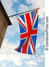 La bandera británica ondeando en el viento. En el fondo del cielo azul con nubes blancas