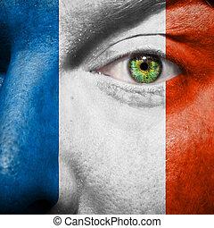 La bandera pintada en la cara con el ojo verde para mostrar apoyo a Francia