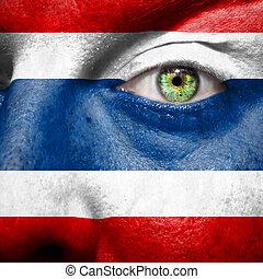 La bandera pintada en la cara con el ojo verde para mostrar apoyo a Tailandia