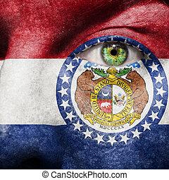 La bandera pintada en la cara con el ojo verde para mostrar apoyo de Missouri
