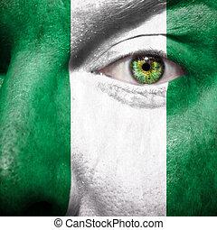 La bandera pintada en la cara con el ojo verde para mostrar apoyo nigeria