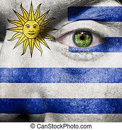 La bandera pintada en la cara con el ojo verde para mostrar apoyo uruguay