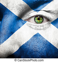 La bandera pintada en la cara con el ojo verde para mostrar el apoyo de Escocia