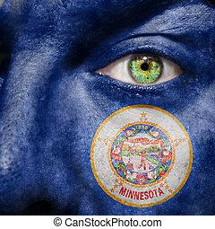 La bandera pintada en la cara con el ojo verde para mostrar el apoyo de Minnesota