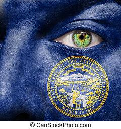La bandera pintada en la cara con el ojo verde para mostrar el apoyo de Nebraska
