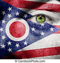 La bandera pintada en la cara con el ojo verde para mostrar el apoyo de Ohio