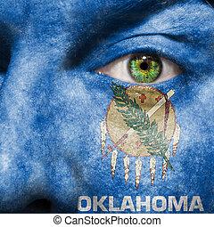 La bandera pintada en la cara con el ojo verde para mostrar el apoyo de Oklahoma